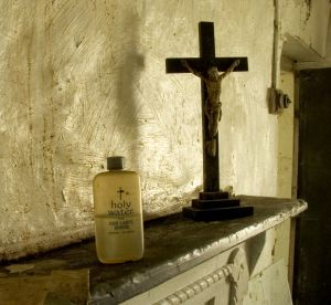 Crucifix and Holy Water on a fireplace mantel.